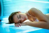 Fotografie mladá žena položila na postel solárium