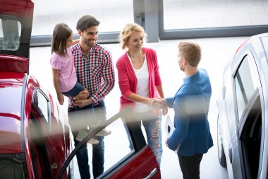 Car dealer offering a car to family