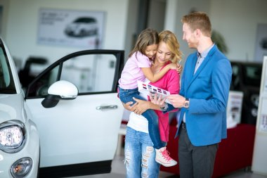 woman with child in  car dealership looking at brochure with sal