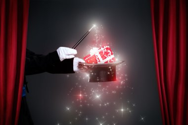 Magician hand with magic wand making Christmas  gift