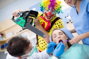 Clown from horror with chainsaw in dental clinic