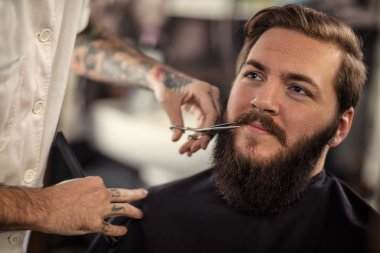 man barber with scissors cut the mustach