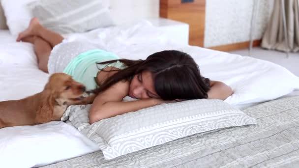 Junge Frau spielt mit einem Hund während der Verlegung auf einem Bett im Haus