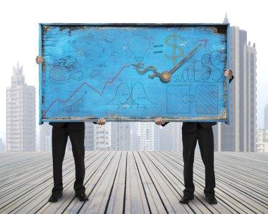 two men holding old blue doodles billboard on skyscraper citysca