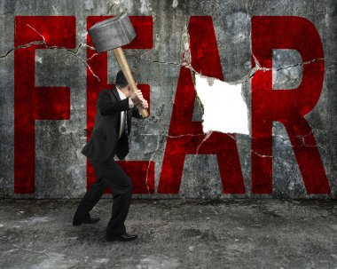 businessman holding sledgehammer hitting red FEAR word on concre