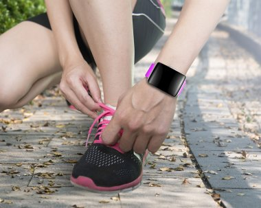 human hand tying shoelaces wearing smartwatch with bright pink w
