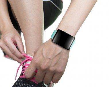 woman hand tying shoelaces wearing smartwatch with bright green