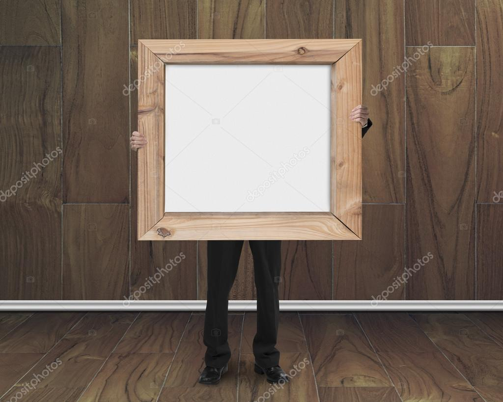 businessman holding blank whiteboard with wood frame in wooden r ...