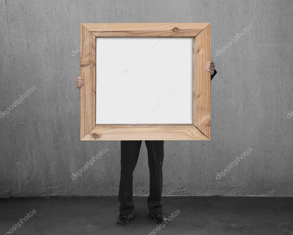 man hold blank whiteboard with wooden frame in concrete room — Stock ...