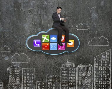 businessman using tablet on black cloud with app icons