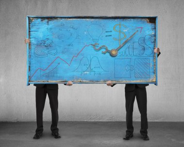 two men holding old blue doodles billboard on concrete wall