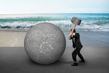 businessman holding hammer hitting cracked concrete ball with se