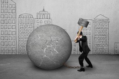 businessman holding hammer hitting cracked concrete ball with bu