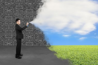 Businessman spraying clouds sky grass paint cover old brick wall