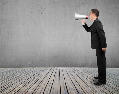 Business man using megaphone yelling with concrete wall wooden f