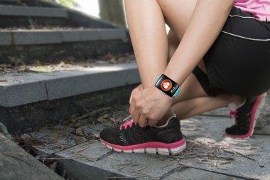 Sport woman tying shoelaces wearing health sensor smartwatch wit