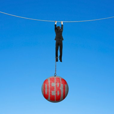 Businessman shackled by debt ball hanging on rope blue backgroun