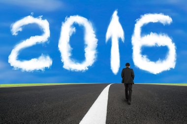 Businessman walking on asphalt road with 2016 arrow sign clouds