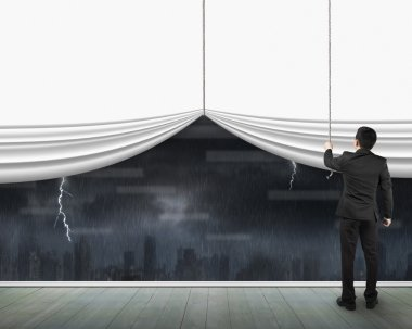 Man pulling open blank white curtain heavy rain dark cityscape