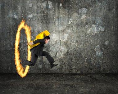 Businessman carrying golden dollar sign jumping through fire hoo