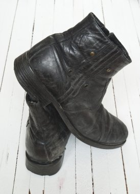 Old boot over white wood floor