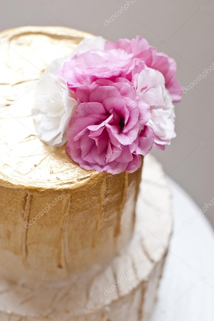 Gold Und Weisse Hochzeitstorte Und Rosa Blumen Rund Um Stockfoto
