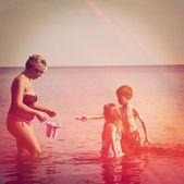 madre e figli camminando sulla spiaggia