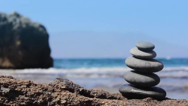 Pyramidy kameny na pláži. Oceán v pozadí