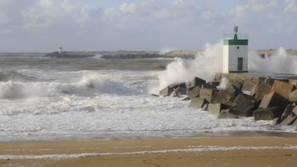 Velké vlny na molo bloků s malým majákem