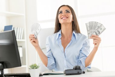 Young businesswoman in office, sitting at an office desk, holding money and with an expression of happiness on her face looking up. stock vector