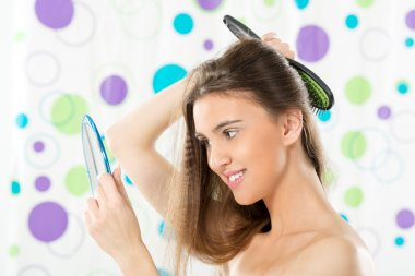 Girl With A Mirror Combing Her Hair