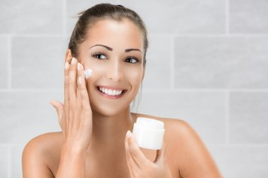 Young Woman Putting Face Cream