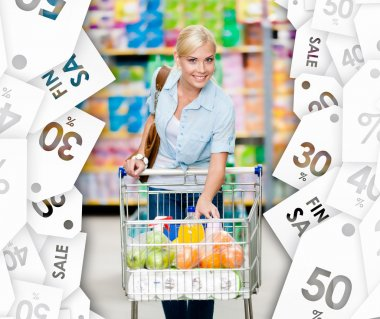 Girl with cart full of food in the shopping center. Sale coupons background
