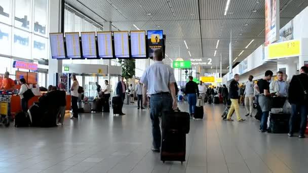 Passenger crowd inside of Amsterdam Airport Schiphol, Amsterdam, Netherlands.