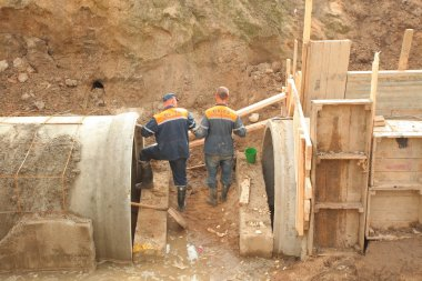 Workers laying collector concrete pipes
