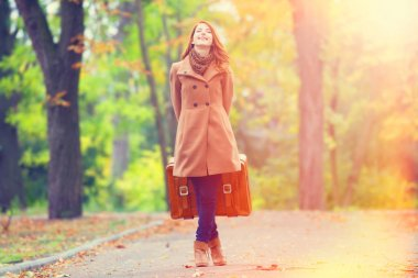 Redhead girl with suitcase at autumn outdoor