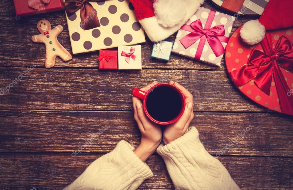 Weibliche Betrieb Tasse Kaffee auf Holztisch nahe Weihnachtsgeschenk ...