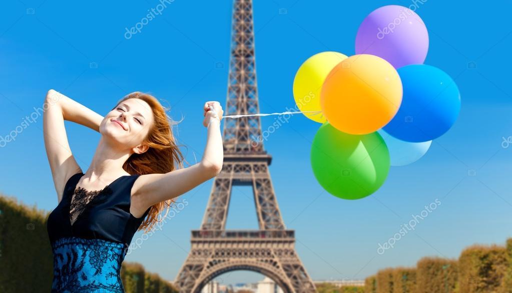 Redhead girl with colour balloons on parisian Eiffel tower backg