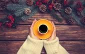 Fényképek Girl gazdaság csésze kávé fenyő ágak közelében