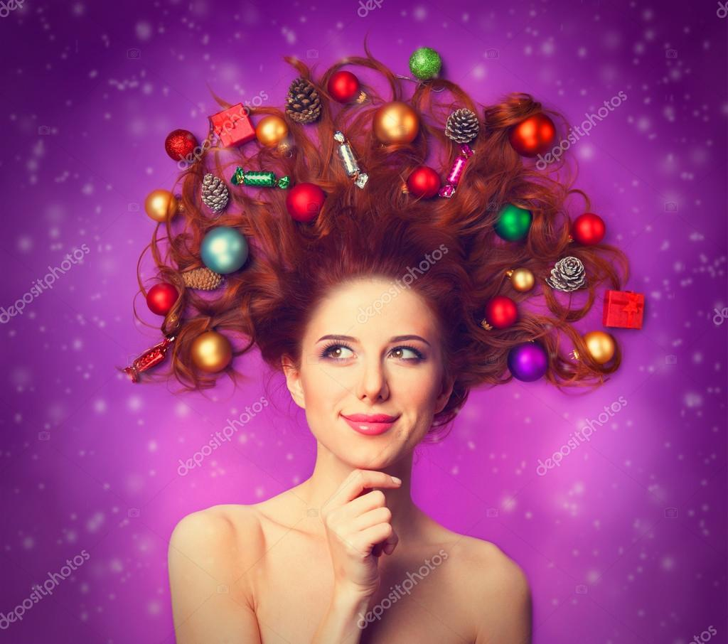 Beautiful redhead girl with christmas toys on violet background.