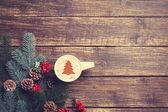 Fotografie Heißer Cappuccino mit Weihnachtsbaum-Form auf einem Holztisch in der Nähe