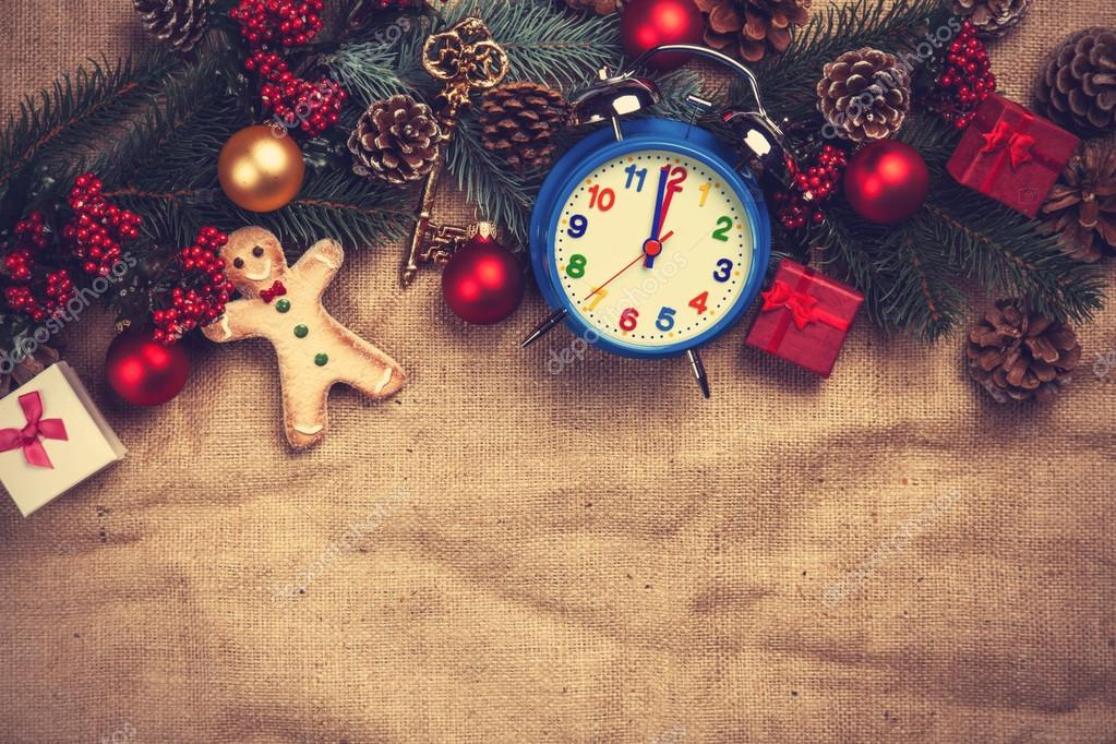 Christmas gifts and alarm clock on jute background.