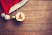 Fotografie Cappuccino mit Weihnachten Hut auf Holztisch