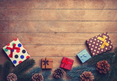 Christmas gifts near pine branch on wooden table.