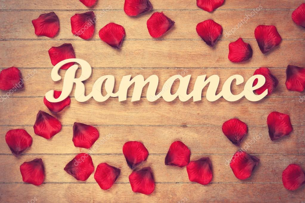 word romance and petals on wooden table stock photo