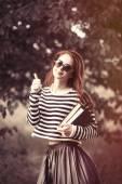 Fotografia ragazza in maglione a strisce con i libri