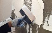 Fotografia Il processo di applicazione di uno stucco bianco sul muro di cemento grigio