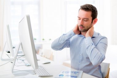 Young attractive man got a neck pain at the office