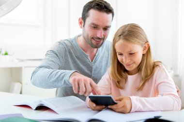 Father helping out her daughter for homework