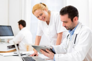 Doctor and an assistant working together at the hospital